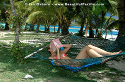 backpacker reading book in hammock at Long Beach Resort